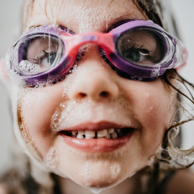 little girl with goggles and bubble bath in the bath tub