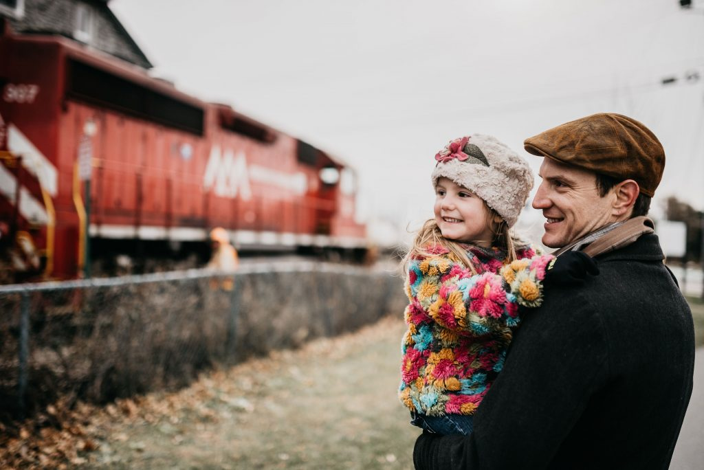 father and daughter watching the train go by in Vermont USA